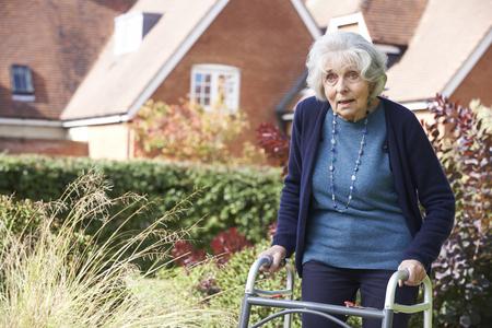 adult 80s: Senior Female In Garden Using Walking Frame Stock Photo