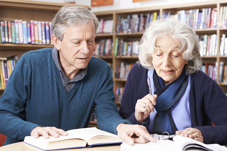 the elderly tutor: Mature Student Working With Teacher In Library Stock Photo