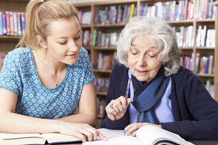 profesor alumno: Mujer mayor que trabaja con el maestro en la biblioteca