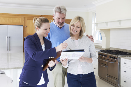 Realtor: Female Realtor Showing Mature Couple Around New Home Stock Photo