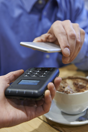 contactless: Man Using Contactless Payment App On Mobile Phone In Cafe