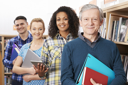 evening class: Group Of Mature Students Studying In Library Stock Photo