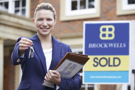 property ladder: Female Realtor Standing Outside Residential Property Holding Keys
