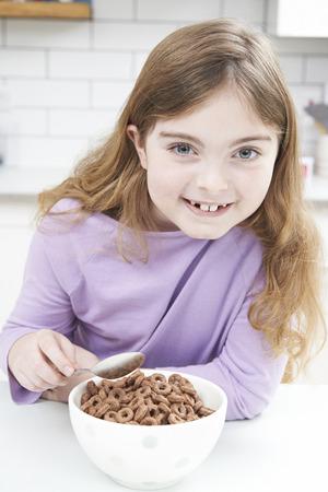 comiendo cereal: Muchacha que come el plato de cereal azucarado en cocina