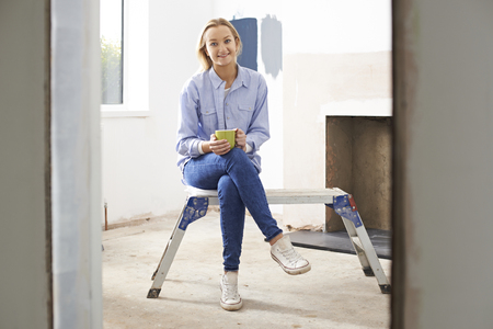 workbench: Woman Sitting In Property Being Rennovated Stock Photo