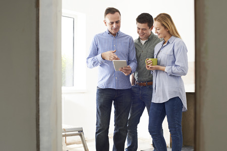 rennovation: Couple Meeting With Architect Or Builder In Rennovated Property Stock Photo