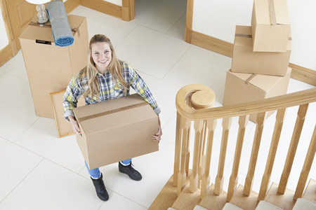 property ladder: Portrait Of Young Woman Moving Into New Home Stock Photo