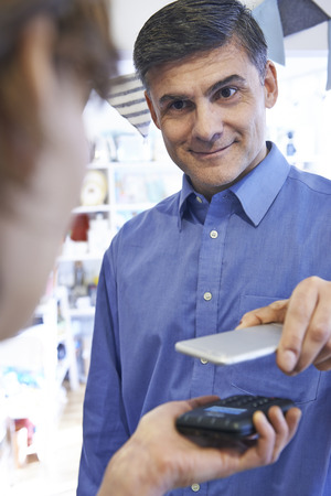 mobile app: Man Using Contactless Payment App On Mobile Phone In Store