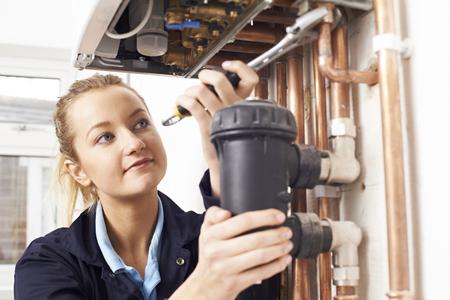 Female Plumber Working On Central Heating Boiler