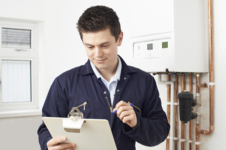 Male Plumber Working On Central Heating Boiler Stock Photo - 56216456