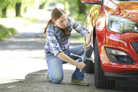 Frustrated Female Driver With Tyre Iron Trying To Change Wheel Archivio Fotografico