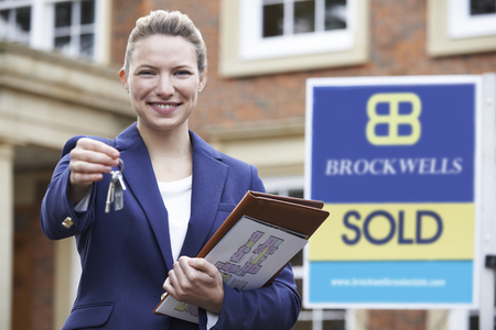 vacant sign: Female Realtor Standing Outside Residential Property Holding Keys