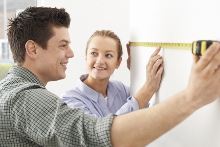 measuring: Young Couple Measuring Wall In New Home