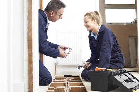 fitting: Plumber And Female Apprentice Fitting Central Heating