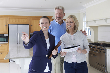 property ladder: Female Realtor Showing Mature Couple Around House Stock Photo