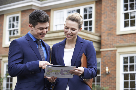 property ladder: Male And Female Realtor Standing Outside Residential Property Stock Photo