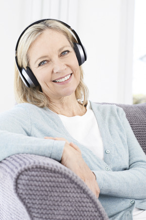 one woman: Mature Woman Listening To Music On Wireless Headphones