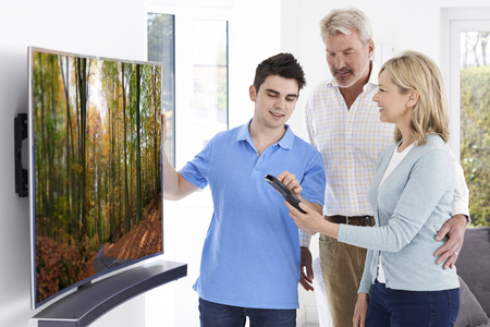 Man Demonstrating New Television To Mature Couple At Home Archivio Fotografico