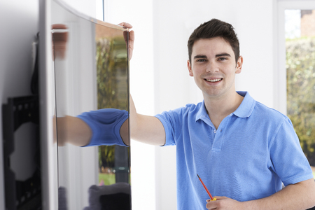 fitting in: Engineer Fitting Curved Screen Television In Home