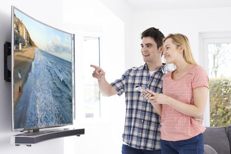 Young Couple With New Curved Screen Television At Home Stock fotó