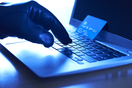 data theft: Cyber Criminal With Stolen Credit Card And Laptop