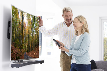 hd tv: Mature Couple With New Curved Screen Television At Home Stock Photo
