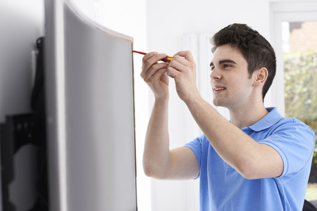 screwdrivers: Engineer Fitting Curved Screen Television In Home