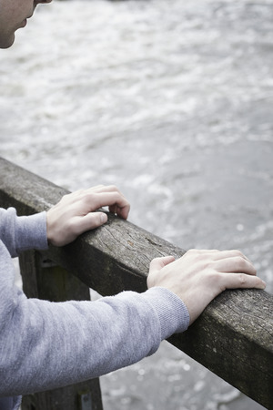 suicidal: Depressed Young Man Contemplating Suicide On Bridge Over River