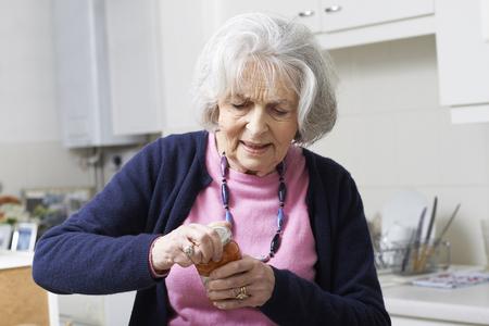 frasco: Mujer mayor que pugnan por llevar a saltar la tapa Foto de archivo