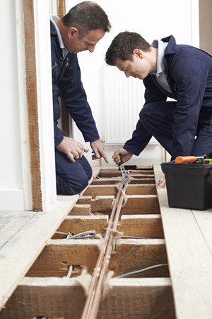 fitting in: Plumber And Apprentice Fitting Central Heating in House Stock Photo