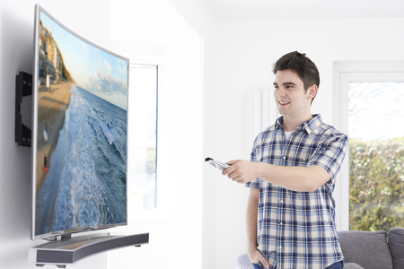 tv home: Young Man With New Curved Screen Television At Home Stock Photo