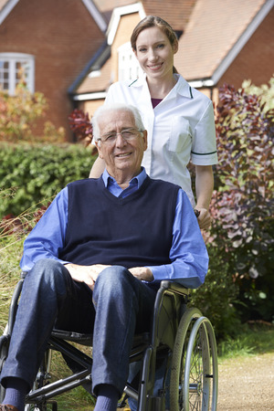 the ageing process: Portrait Of Carer Pushing Senior Man In Wheelchair Stock Photo