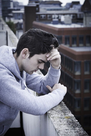 social emotional: Depressed Young Man Contemplating Suicide On Top Of Tall Building Stock Photo