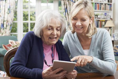 80s adult: Female Neighbor Showing Senior Woman How To Use Digital Tablet Stock Photo