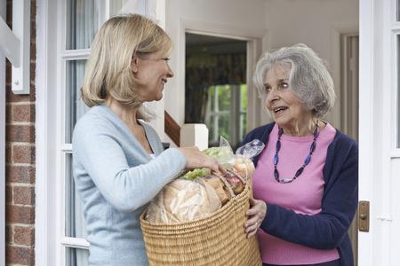 쇼핑과 함께 노인 여성을 돕는 여성 이웃