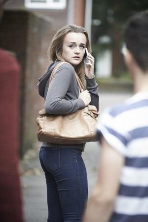 intimidated: Teenage Girl Using Phone As She Feels Intimidated On Walk Home