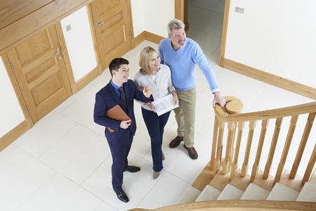 high angle: Showing Mature Couple Around House For Sale