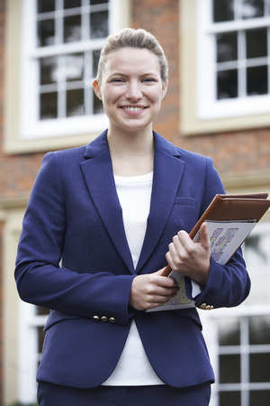 property ladder: Portrait Of Female  Standing Outside Residential Property