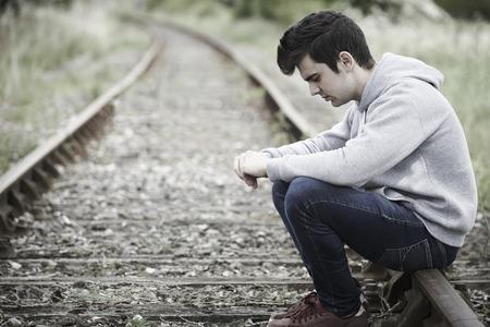 Depresso giovane, seduto sulla Ferrovia