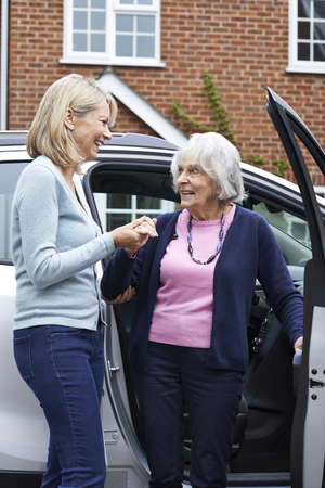 adult offspring: Female Neighbor Giving Senior Woman A Lift In Car Stock Photo