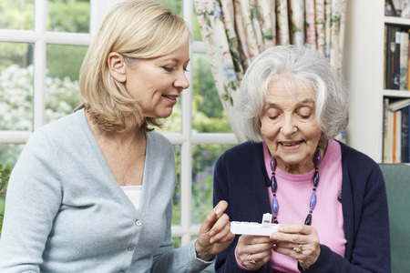neighbor: Female Neighbor Helping Senior Woman With Medication Stock Photo