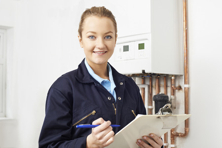 Female Plumber Working On Central Heating Boiler Stock fotó - 57482889