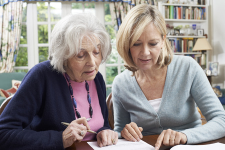80s adult: Female Neighbor Helping Senior Woman To Complete Form