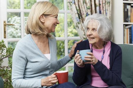 Mujer que toma el tiempo para visitar Vecina mayor e Talk