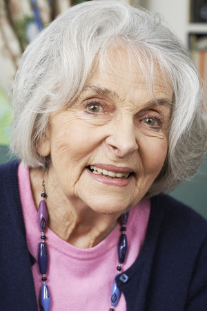 one woman: Head And Shoulders Portrait Of Smiling Senior Woman At Home Stock Photo