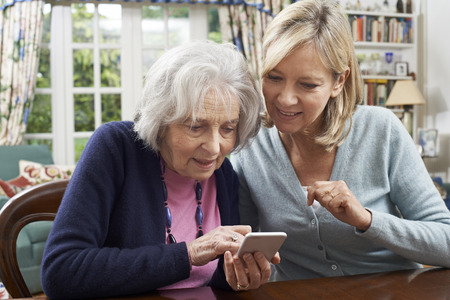adult offspring: Woman Helping Semior Neighbor To Use Mobile Phone