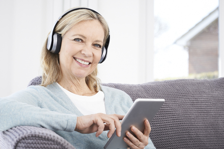 fil: Mature Woman Streams Music From Digital Tablet To Wireless Headphones Stock Photo