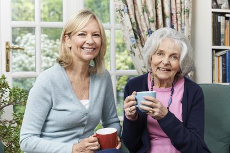 Frau Zeit nehmen Ältere Nachbarin zu besuchen und Diskussion Standard-Bild