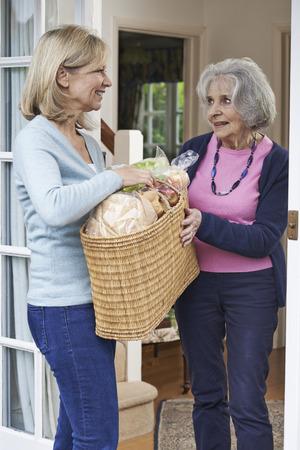 neighbor: Female Neighbor Helping Senior Woman With Shopping