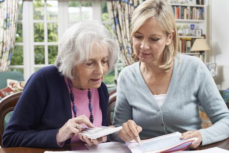 tercera edad: Mujer madura Ayudando a Vecino mayor con Finanzas de casa